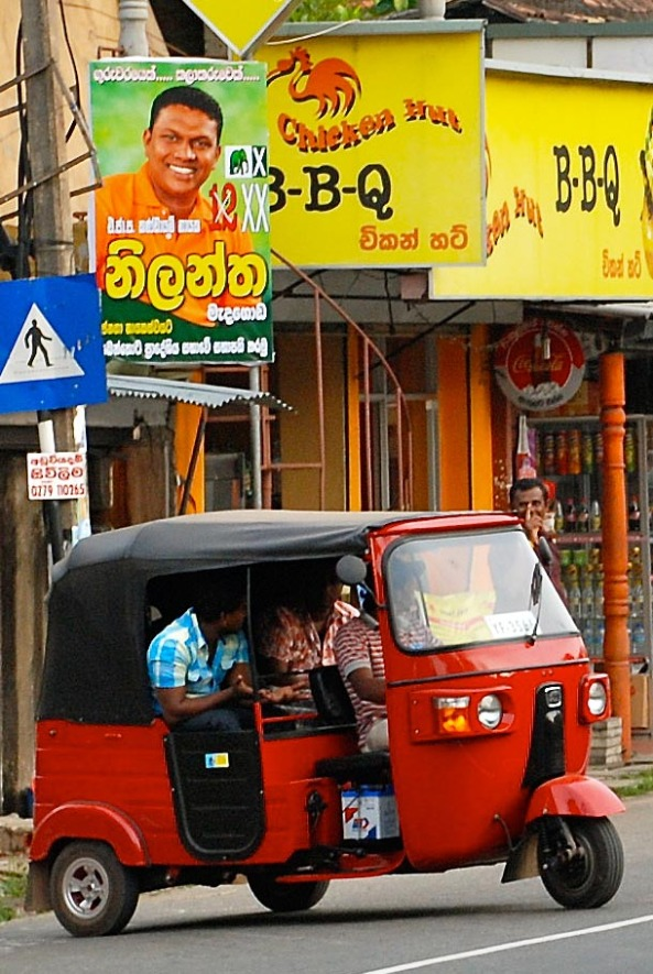 A bright red tuk-tuk on Srilankan roads
