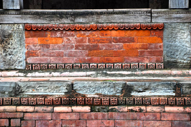 Red bricks, intricate wooden carvings of the Mahasthan Ghar