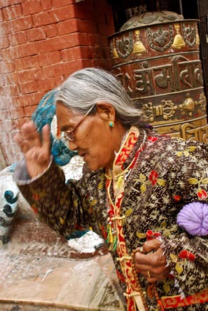 A Buddhist practitioner walks past after spining a prayer wheel